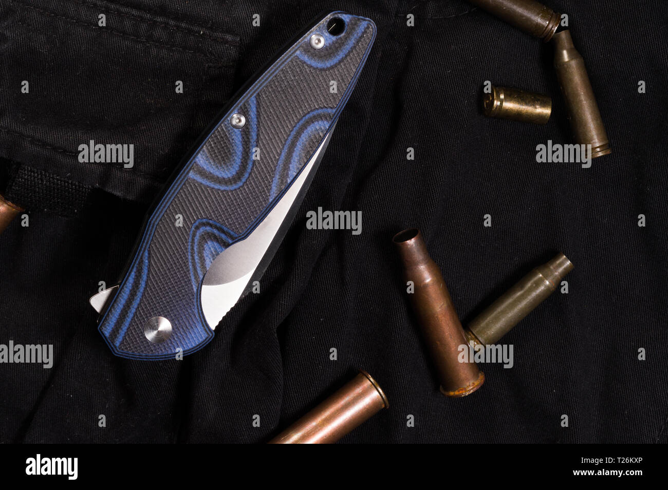 Pocket knife in the folded state. The handle of the knife on the clothes. Top. - Stock Image