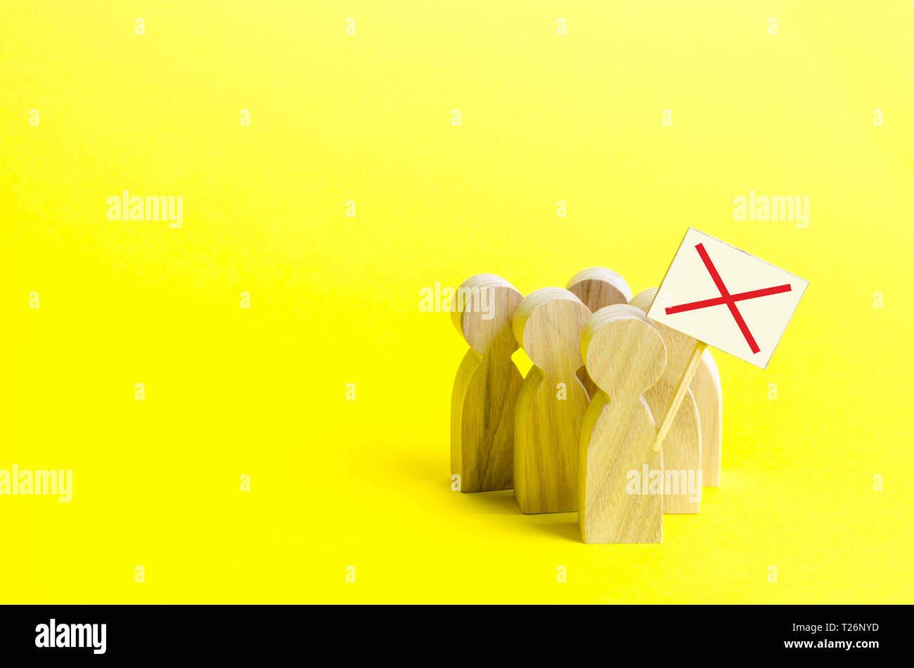 A group of protesting figures with signs on an yellow background. An angry mob of wooden figures of people with a poster. Social discontent and social Stock Photo