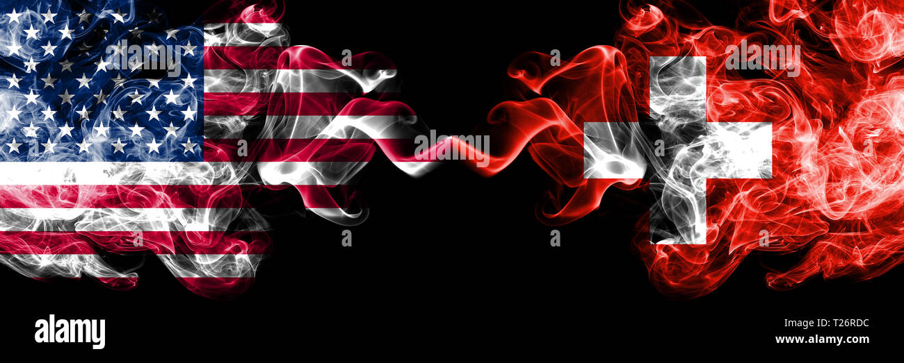 United States of America vs Switzerland, Swiss smoky mystic flags placed side by side. Thick colored silky smoke flags of America and Switzerland, Swi - Stock Image