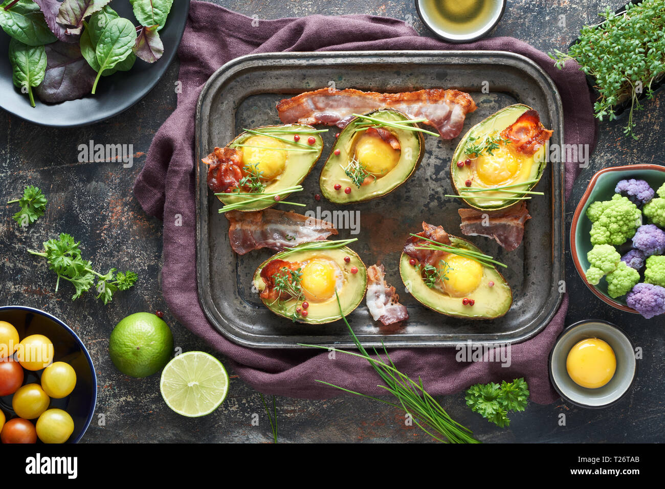 Baked avocado with egg and bacon on a metal baking tray, flat lay with ingredients and herbs on dark background Stock Photo