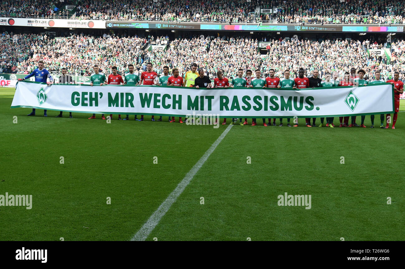 Bremen, Germany. 30th Mar, 2019. Soccer: Bundesliga, Werder Bremen - FSV Mainz 05, 27th matchday. Players of both teams hold a banner 'Go away with racism' in their hands before the start of the game. Credit: Carmen Jaspersen/dpa - IMPORTANT NOTE: In accordance with the requirements of the DFL Deutsche Fußball Liga or the DFB Deutscher Fußball-Bund, it is prohibited to use or have used photographs taken in the stadium and/or the match in the form of sequence images and/or video-like photo sequences./dpa/Alamy Live News - Stock Image