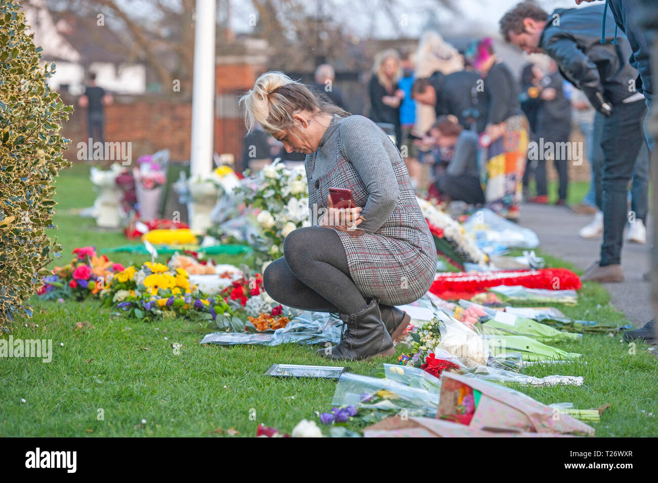 Essex, UK. 30th March 2019. Fans look at the floral tribute in the church grounds after the funeral of the late  Prodigy singer Keith Flint at St Marys Church in Bocking,  Essex today. Credit: Phil Rees/Alamy Live News - Stock Image