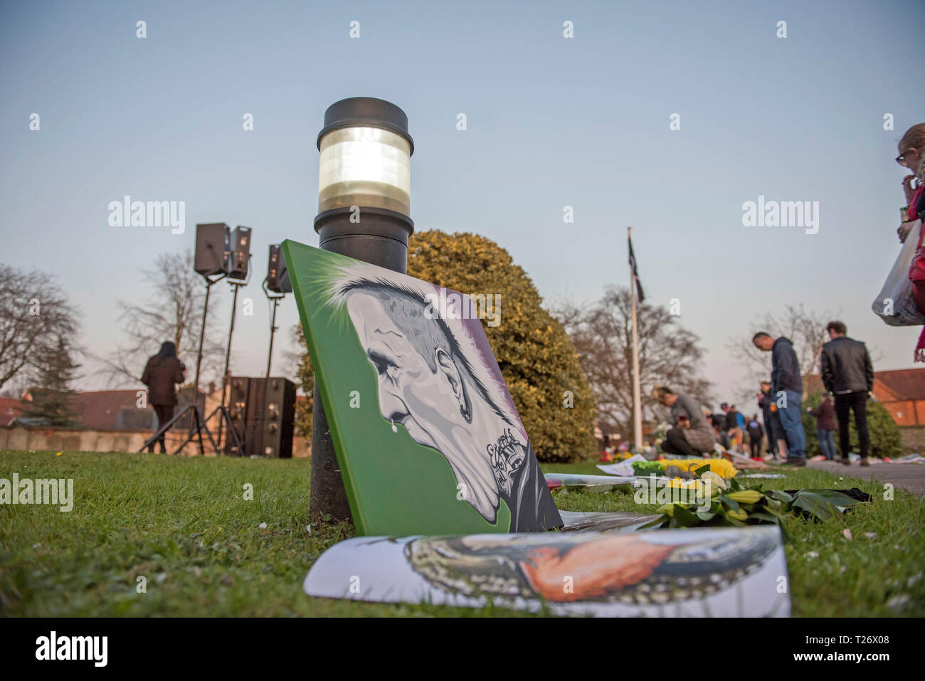 Essex, UK. 30th March 2019. Fans look at the floral tributes in the church grounds after the funeral of the late  Prodigy singer Keith Flint at St Marys Church in Bocking,  Essex today. Credit: Phil Rees/Alamy Live News - Stock Image