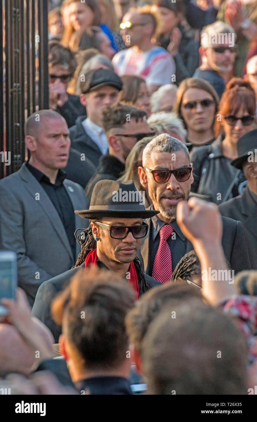 Essex, UK. 30th March 2019. The  funeral of Prodigy singer Keith Flint at St Marys Church in Bocking,  Essex today. Mourners leave the service and band members Maxim (Keith Palmer) and Leeroy Thornhill can be seen leaving through the  front gates of the church. Credit: Phil Rees/Alamy Live News - Stock Image