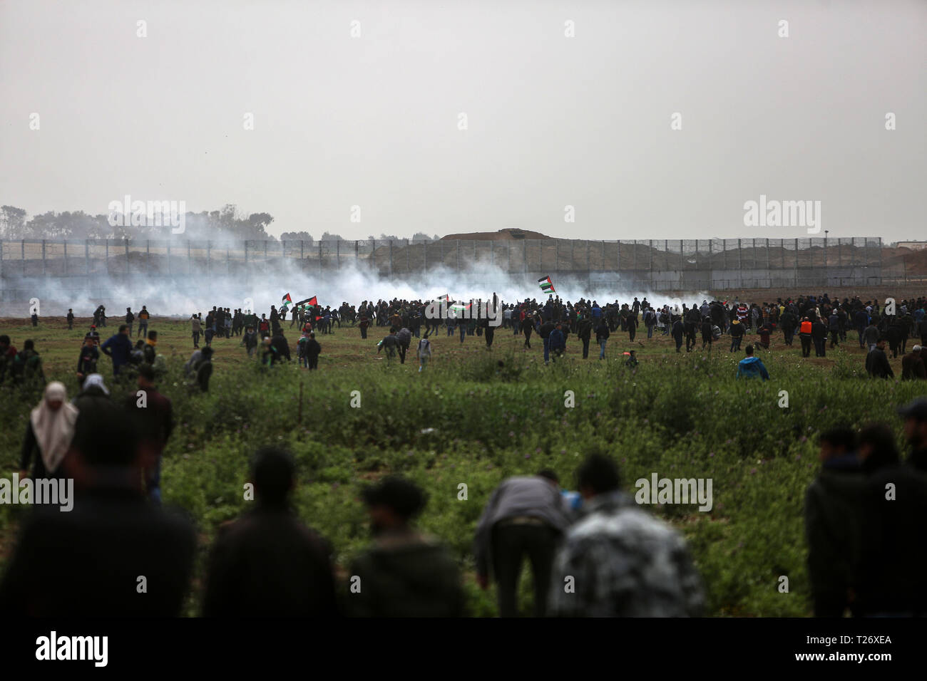 Gaza. 30th Mar, 2019. Palestinian protesters clash with Israeli troops on the Gaza-Israel border, east of Gaza City, March 30, 2019. Thousands of Palestinians marked on Saturday the Palestinian Land Day and the first anniversary of the Palestinian Great March of Return. Credit: Stringer/Xinhua/Alamy Live News - Stock Image