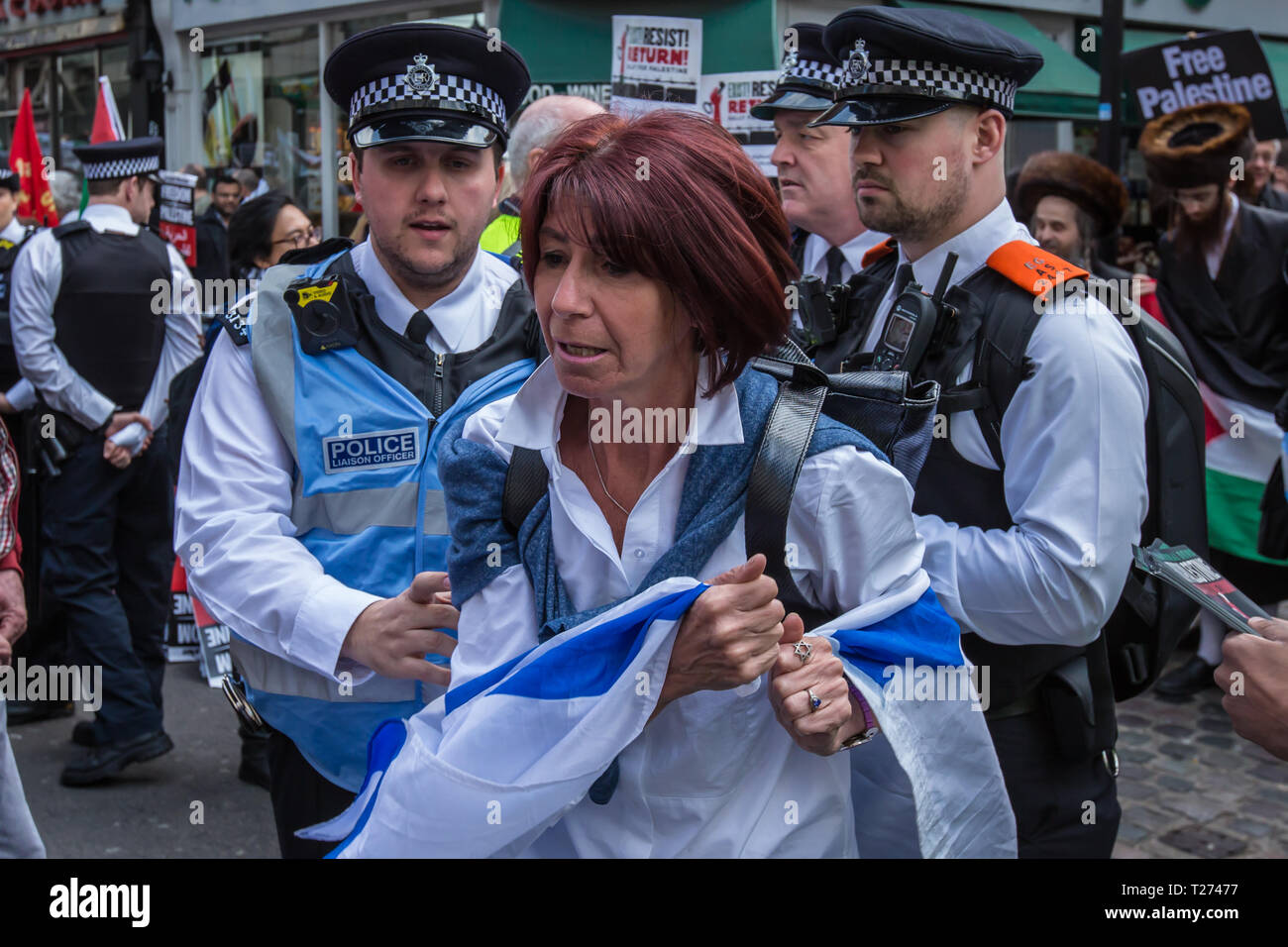 London, UK. 30 March, 2019. A woman with an Israeli flag is removed by the police. Palestinians and supporters gathered outside of the Israeli Embassy in London to mark the beginning of Nakba and to call on the global community to hold Israel to account for their violation of human rights and International law. David Rowe/ Alamy Live News. - Stock Image