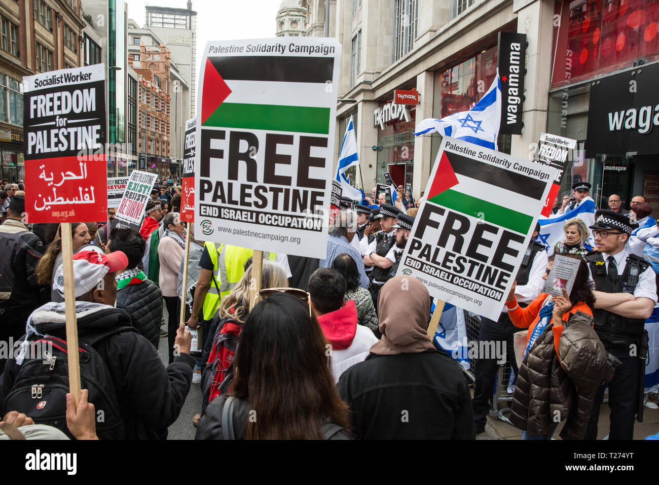 London, UK. 30th March, 2019. Pro-Palestinian campaigners attending a Rally for Palestine outside the Israeli embassy to demand freedom, justice and equality for the Palestinian people stand in front of a small pro-Israel counter-protest Credit: Mark Kerrison/Alamy Live News - Stock Image