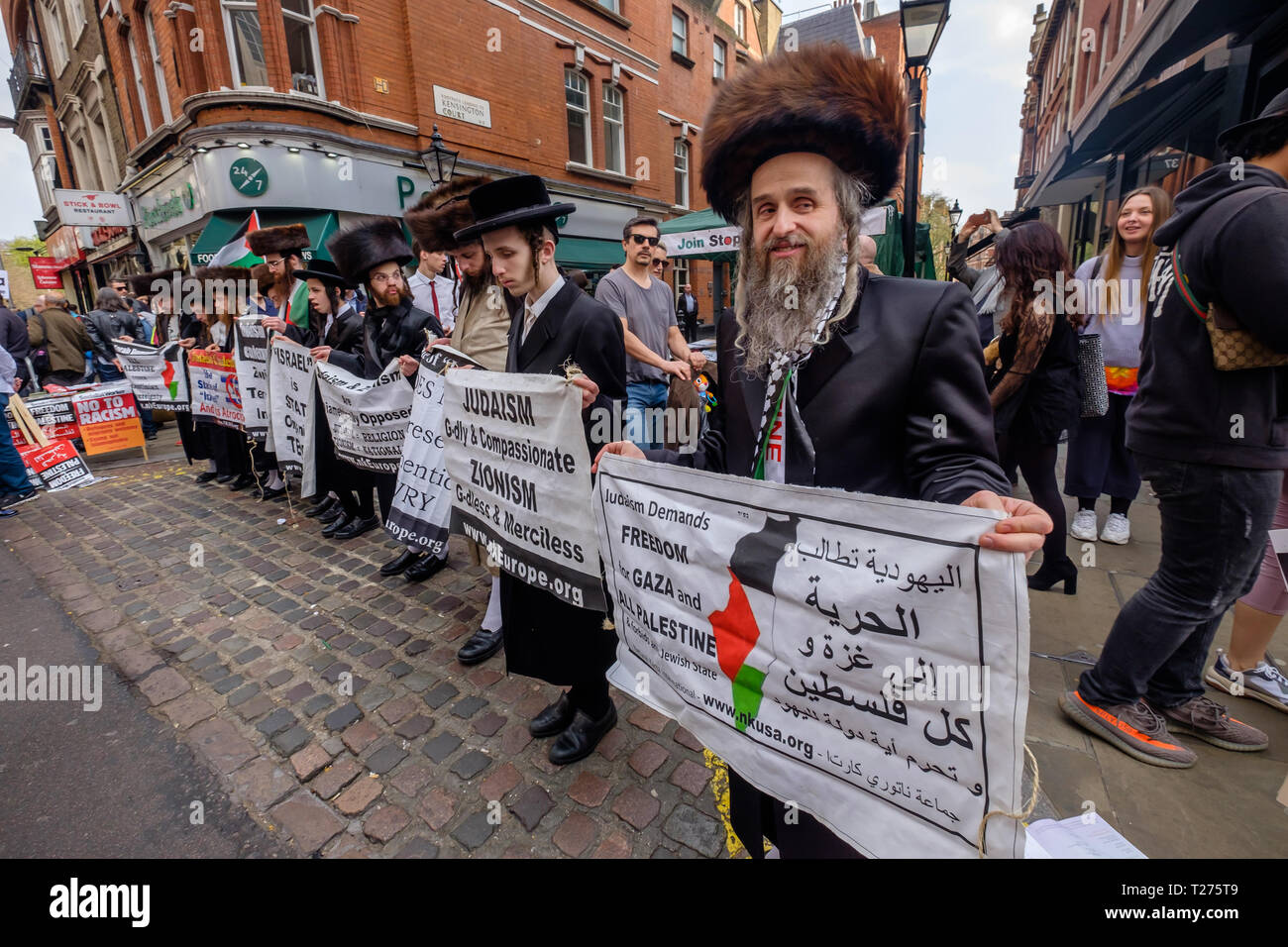 London, UK. 30th March 2019. Neturei Karta ultra-orthodox Jews show their solidarity with the Palestinian people against the Zionist state of Israel, which they say does not represent authentic Jewry. They condemn the atrocities which the Israeli state is committing in Gaza and say that Judaism demands freedom in Gaza and all Palestine and had come to support the Palestinian Land Day protest. While I was there police led away a Zionist who had come to shout anti-semitic comments at them as they stood in silence holding their posters. Peter Marshall Alamy Live News Credit: Peter Marshall/Alamy  - Stock Image
