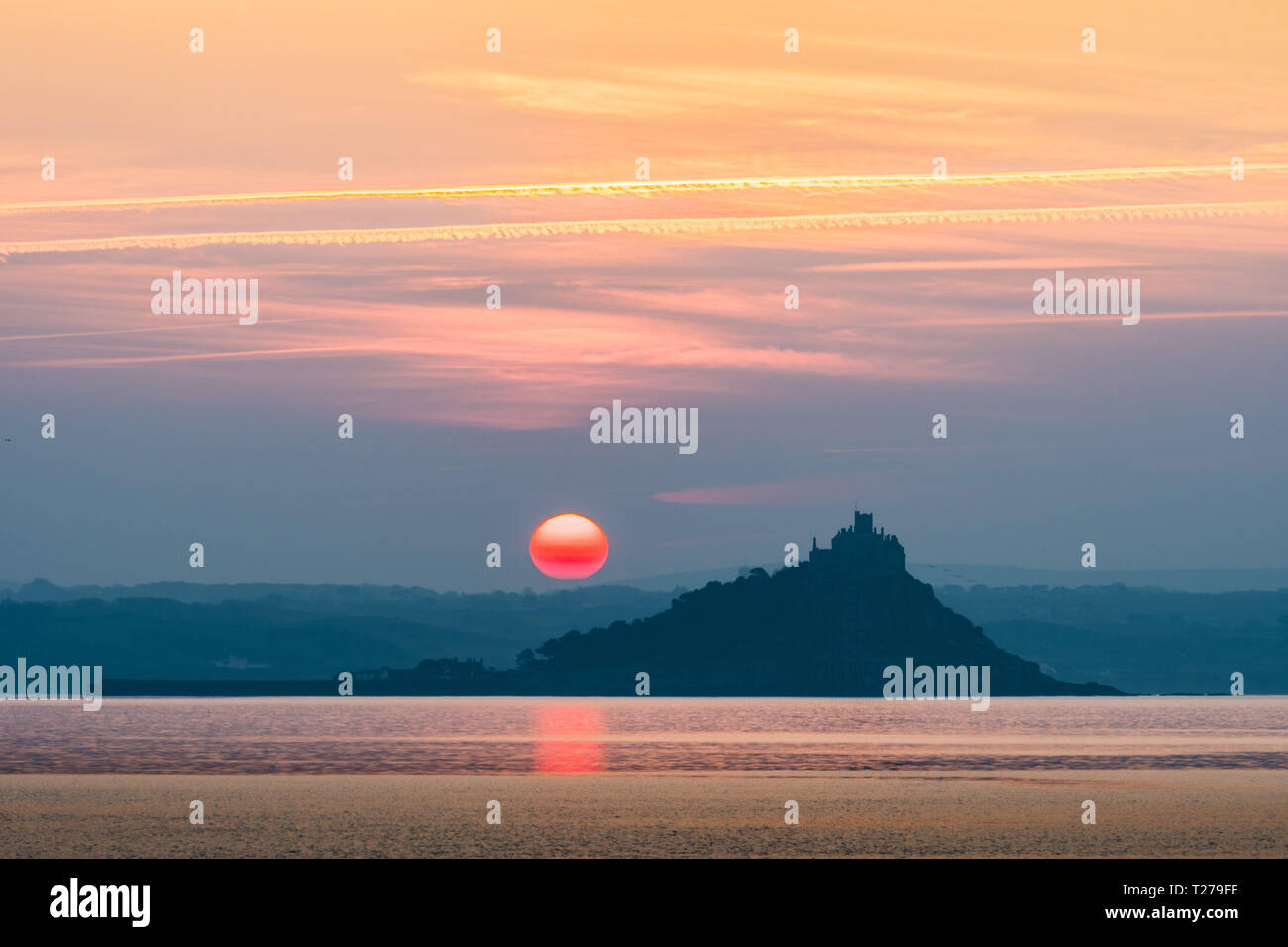 Red sun rising beside St Michaels Mount Cornwall reflecting in the sea Stock Photo