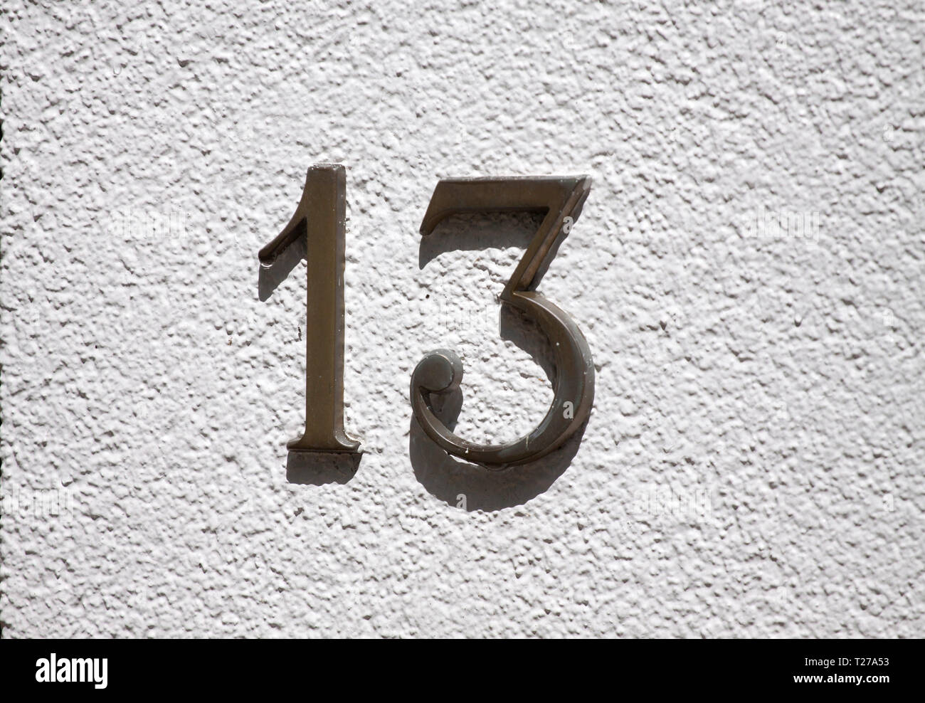 Brass house number 13 screwed on a white wall - Stock Image