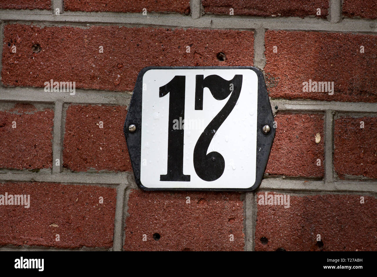 House number plate 17 screwed onto a brick wall - Stock Image