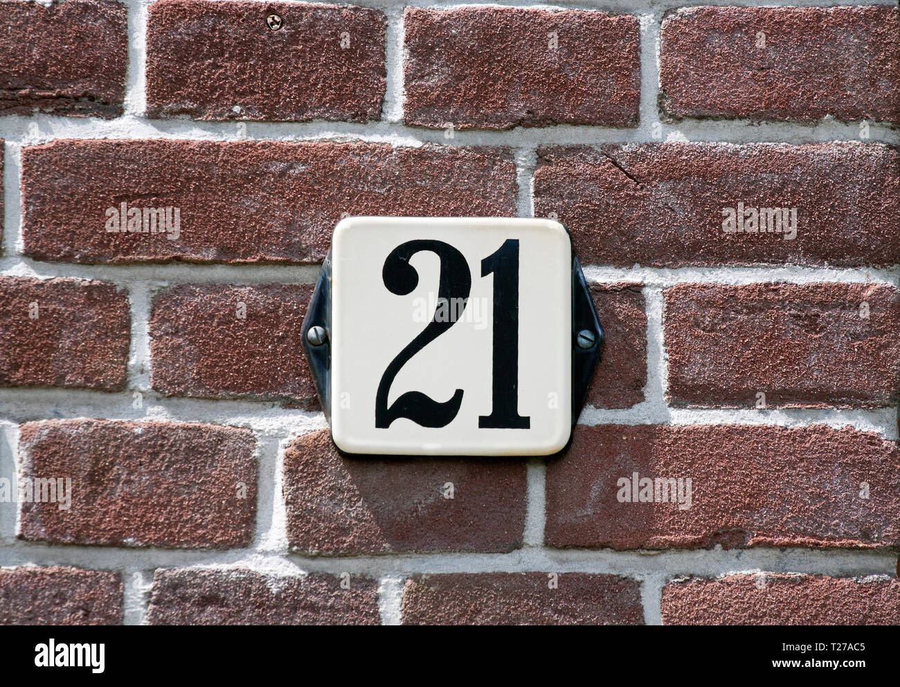 House number plate 21 screwed onto a brick wall - Stock Image