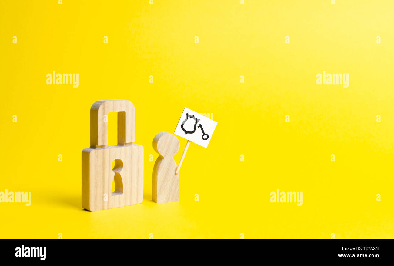A wooden padlock and a person with a poster is trying to authenticate or bypass the protection. the preservation of secrets, information and values. P - Stock Image