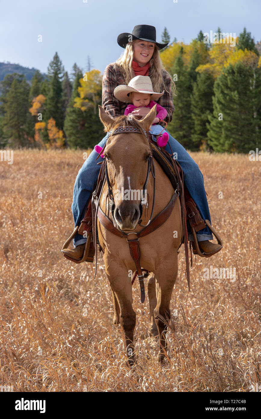 Cowgirl and baby on horseback in Wyoming, USA - Stock Image