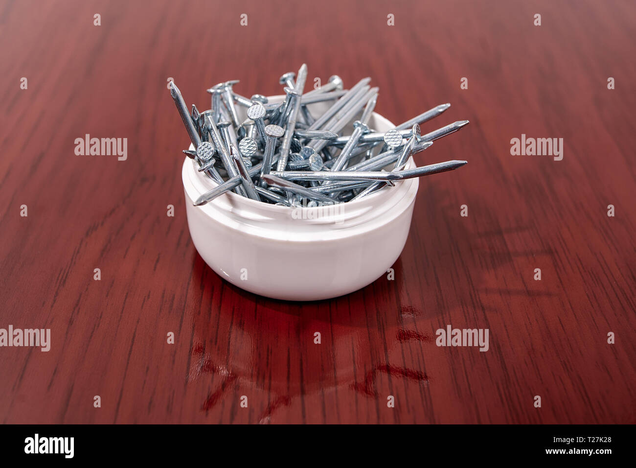 A group of nails (lace) in a bowl on a wooden surface finish - Stock Image