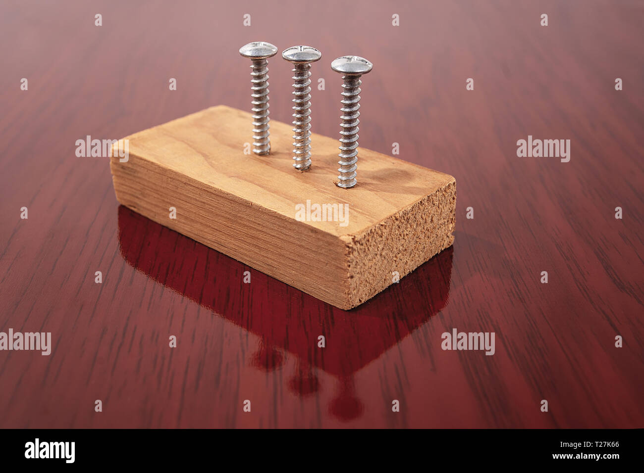 Three screws screwed into a piece of wood on a wooden finish surface - Stock Image