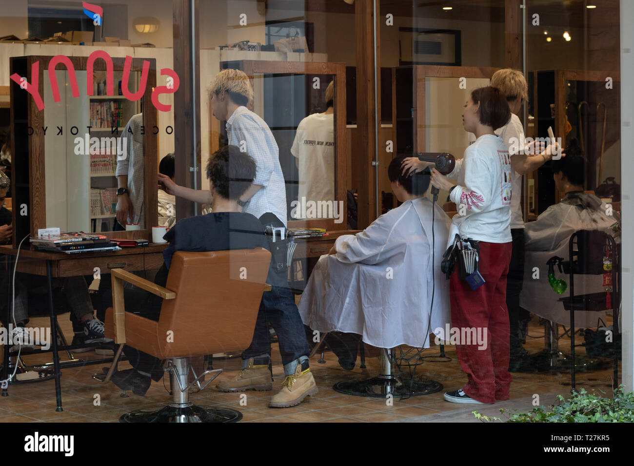 As much as the streets around were maximally crowded, the hair salon was busy with people getting fashionably haircuts. Stock Photo