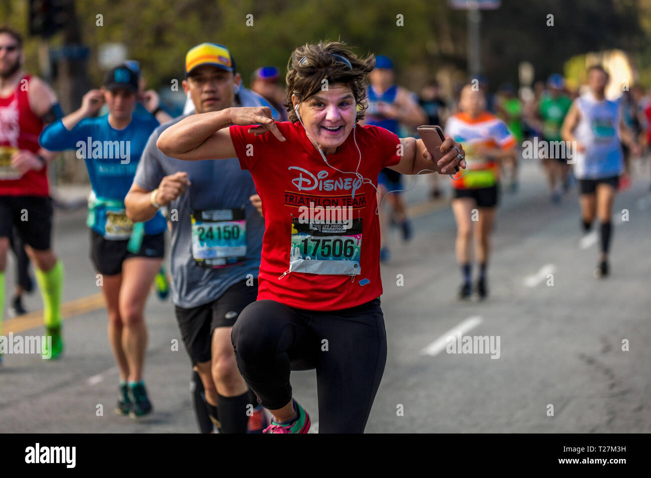 MARCH 24, 2019, LOS ANGELES, CALIFORNIA, USA -  34th Los Angeles Marathon, 'Stadium to the Sea' - the 4th largest in USA and 10th in world - runner waves acknowledges camera - Stock Image