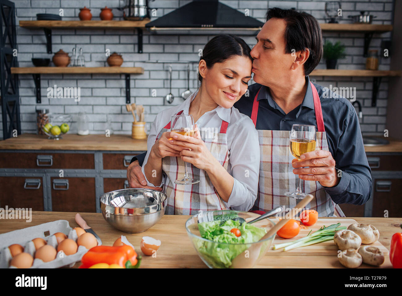 Lovely picture of man sitting with woman together at table in kitchen. He kiss her forehead and hold glass on wine in hand. woman lean to him and enjo Stock Photo