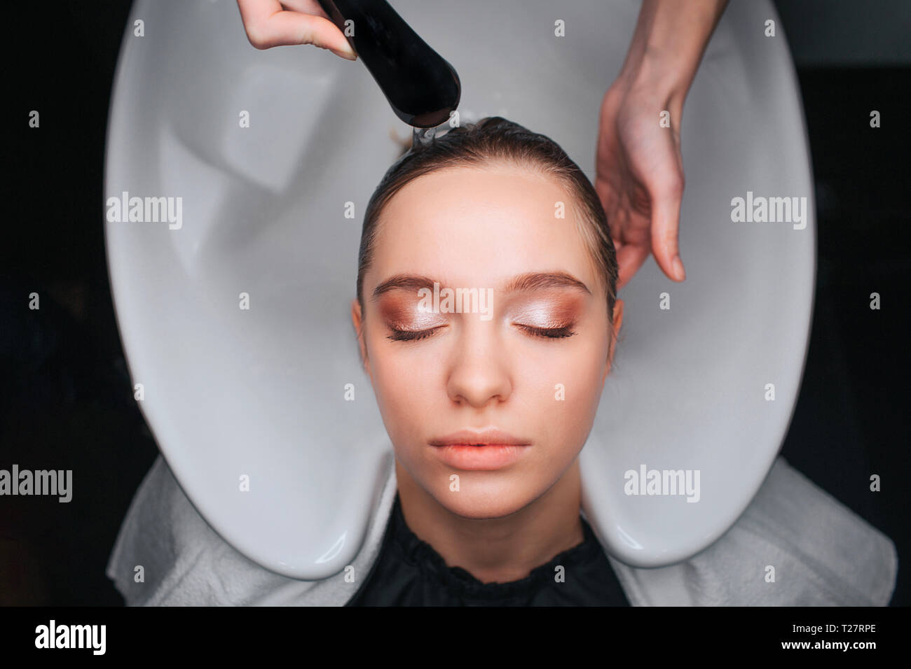 Top view of beautiful young woman with closed eyes sitting on white hair wash sink while hairdresser washing her hair. Hair care in salon - Stock Image
