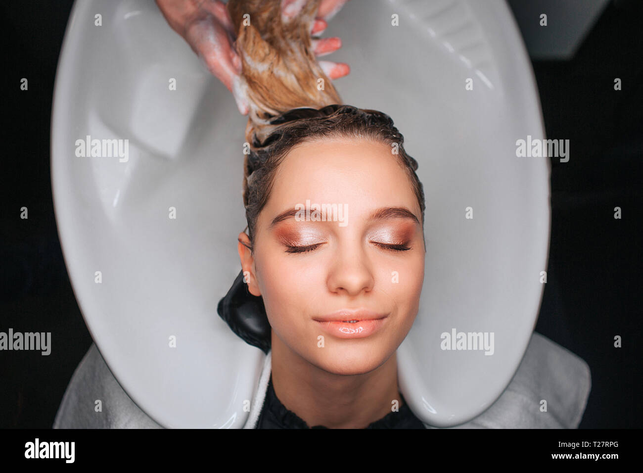 Top view of beautiful young woman with closed eyes smiling while hairdresser washing blonde hair. Hair care in salon - Stock Image