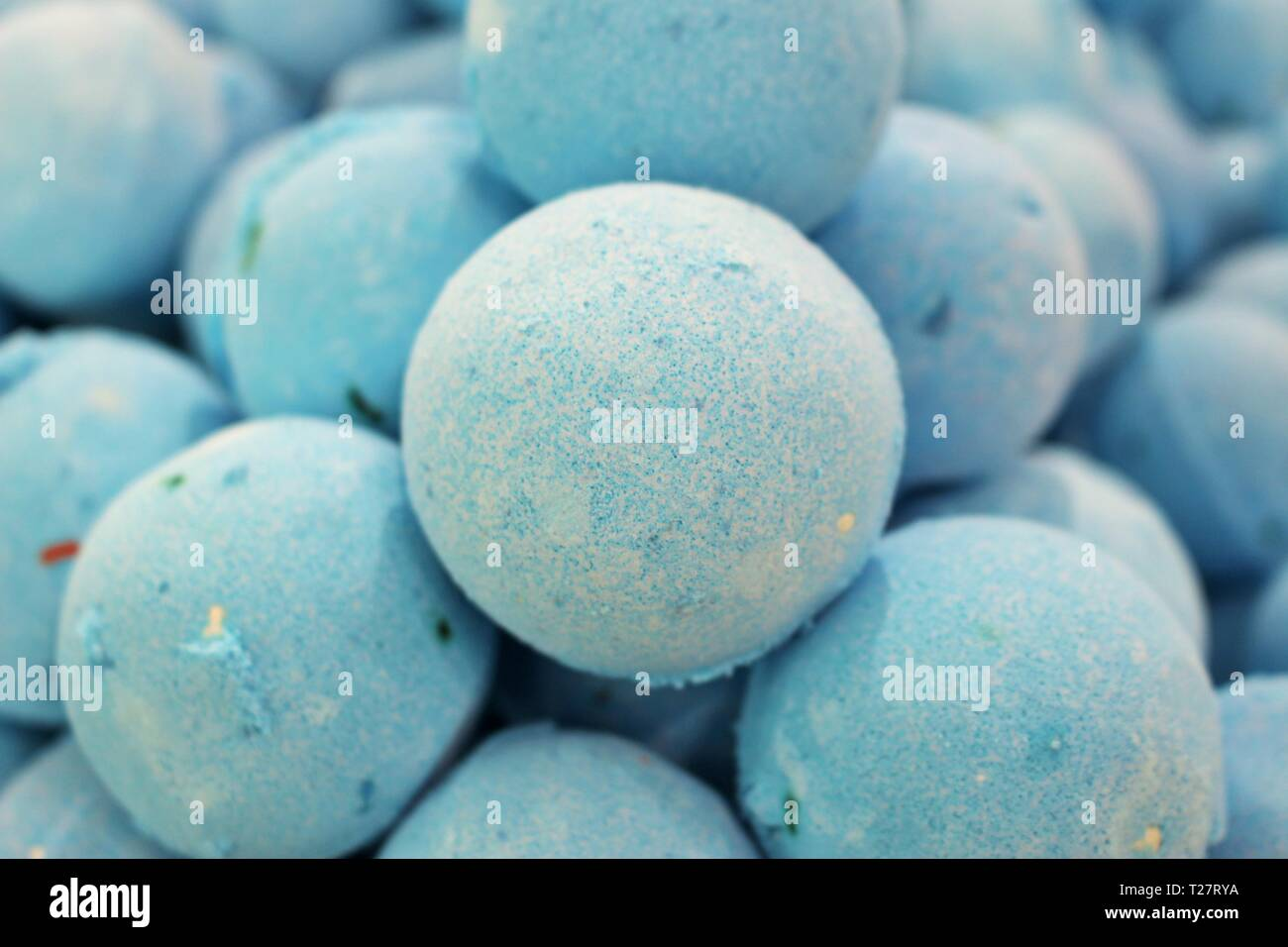 Close up photo of a stack of large, blue bath bombs at a wellness spa - Stock Image