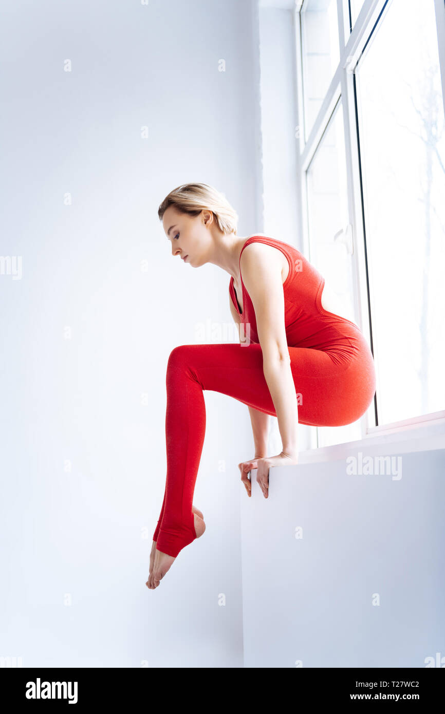 Nice young woman holding on to the windowsill - Stock Image