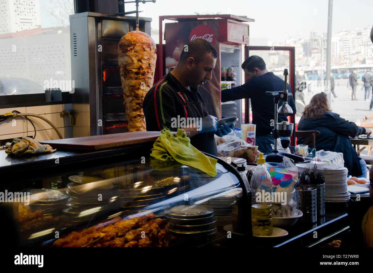 Istanbul,Turkey,March 07,2019:inside of restaurant near Egyptian Bazaar,worker in protective gloves standing at counter looks at the phone - Stock Image