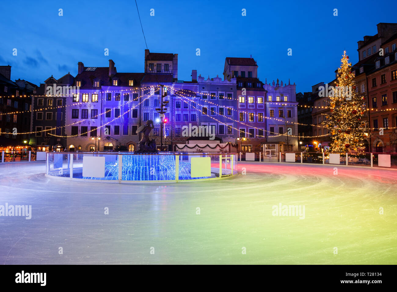 Ice skating rink on Old Town Square in city of Warsaw at night during Christmas time in Poland. - Stock Image