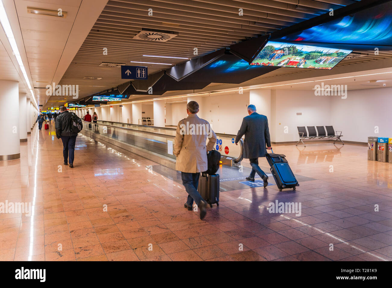 Brussels, Belgium, March 2019 Brussels airport, people are going for customs checks in long corridor with moving walkway, arrival area - Stock Image