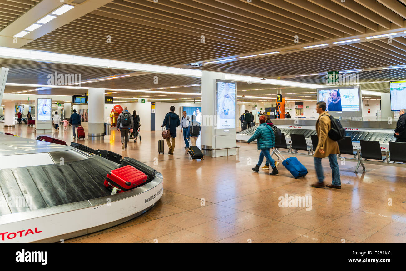 Brussels, Belgium, March 2019 Brussels airport, people collecting their baggage from conveyer after arriving, arrival area, motion blur - Stock Image