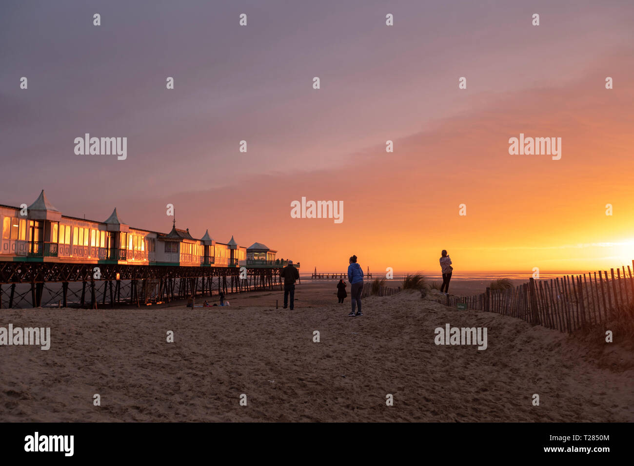 Taking pictures to St Anne's Pier, a Victorian pier, at sunset in the English seaside resort of St Anne's-on-the-Sea, Lytham St Annes, Lancashire, UK - Stock Image