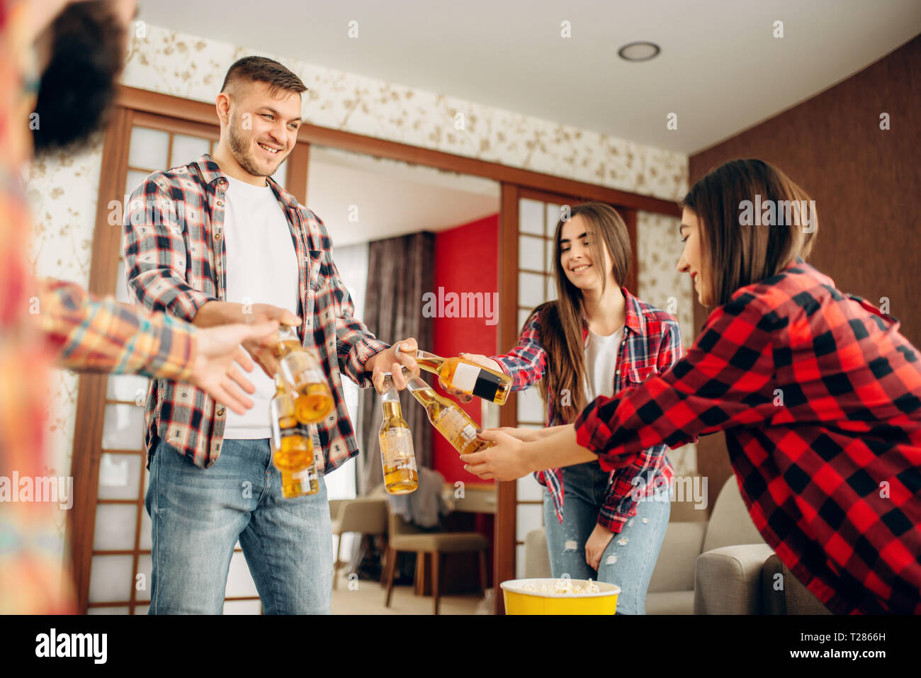 Friends with beer, pizza and popcorn at the home party. Good friendship, group of people leisures - Stock Image