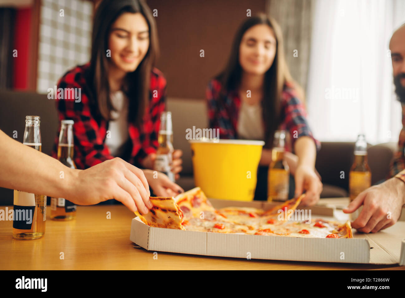 Smiling friends drinks beer with pizza at the house party. Good friendship, group of people leisures together. Cheerful company celebrate the event - Stock Image