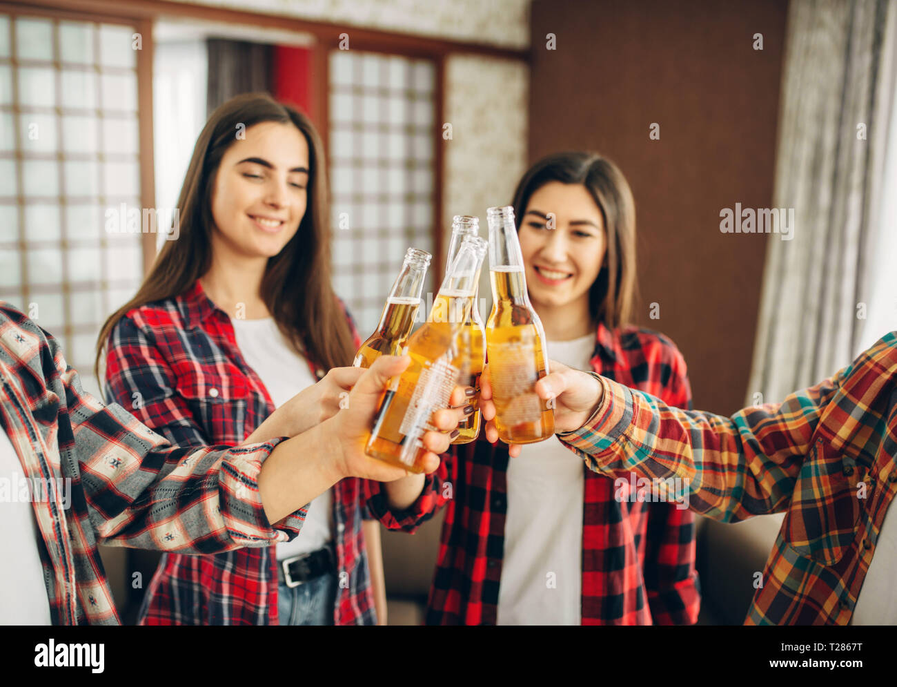 Smiling friends clink bottles with beer at the home party. Good friendship, group of people leisures together. Cheerful company having fun - Stock Image