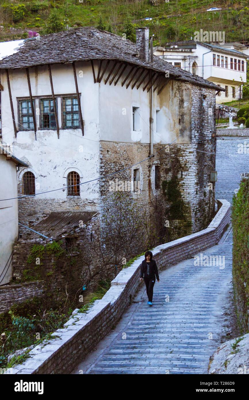 Gjirokaster, Albania : People walk past traditional Ottoman buildings characteristic of the historical center of Gjirokaster. Historic Centres of Bera - Stock Image