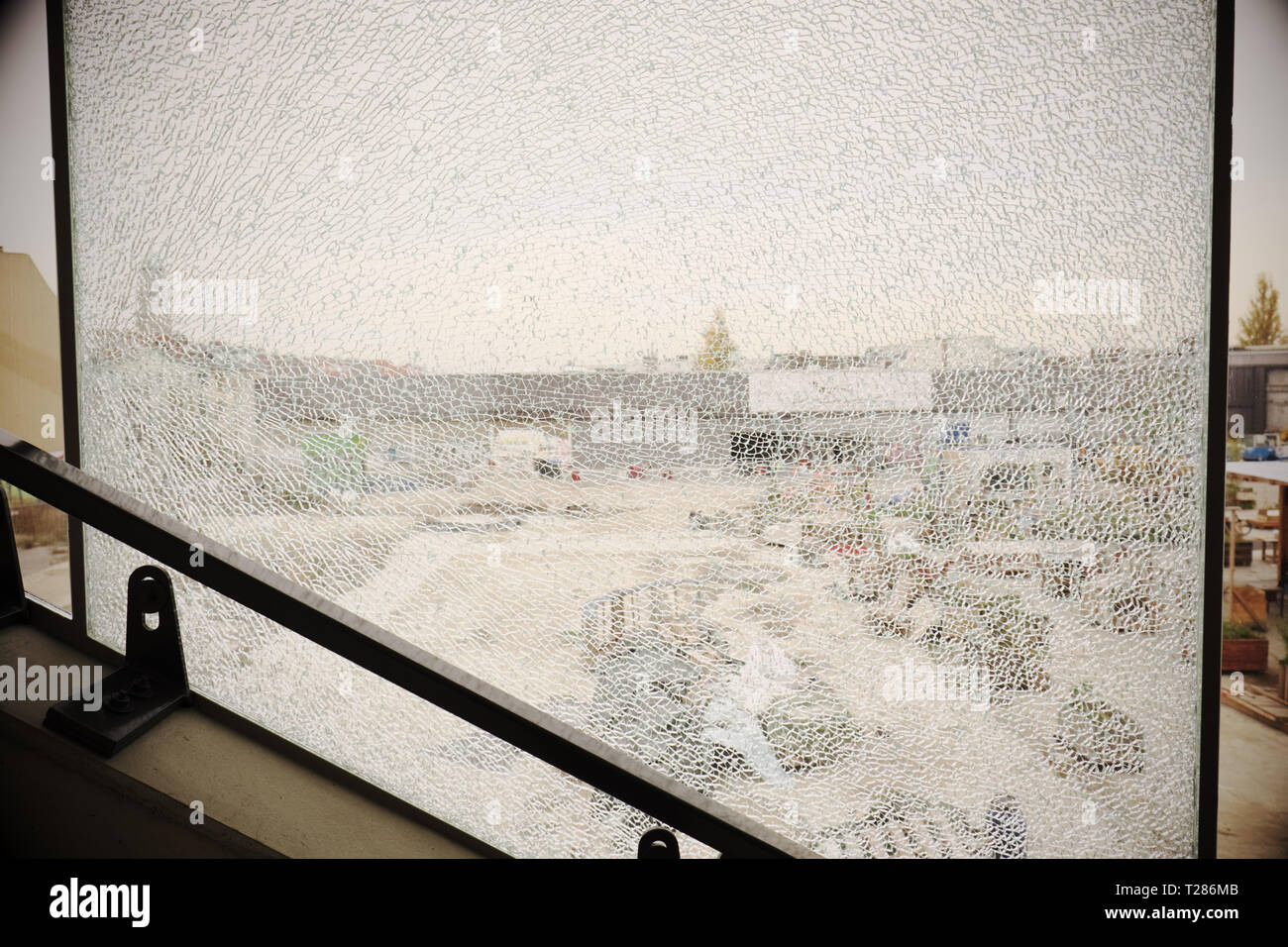 Broken smashed window pane in urban location - Stock Image