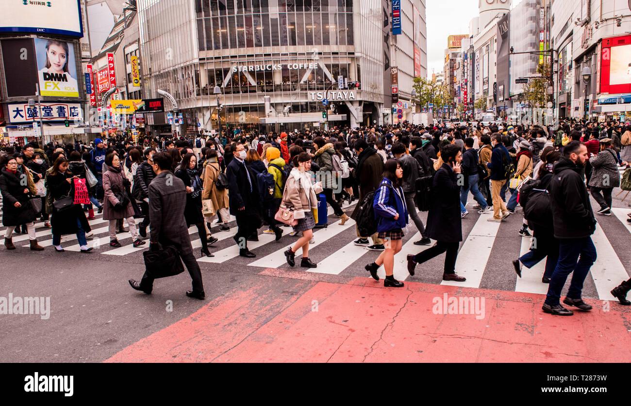 Crowd of people, walking in various directions, crossing the Shibuya crossing, Tokyo, Japan - Stock Image
