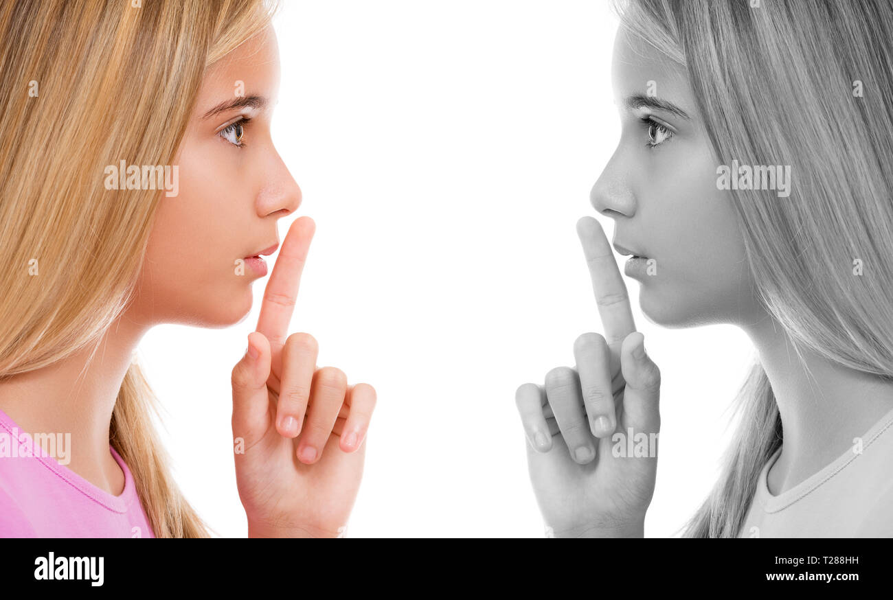 Double portrait of young girl in profile with finger on lips as concept of ordering silence over white background - Stock Image