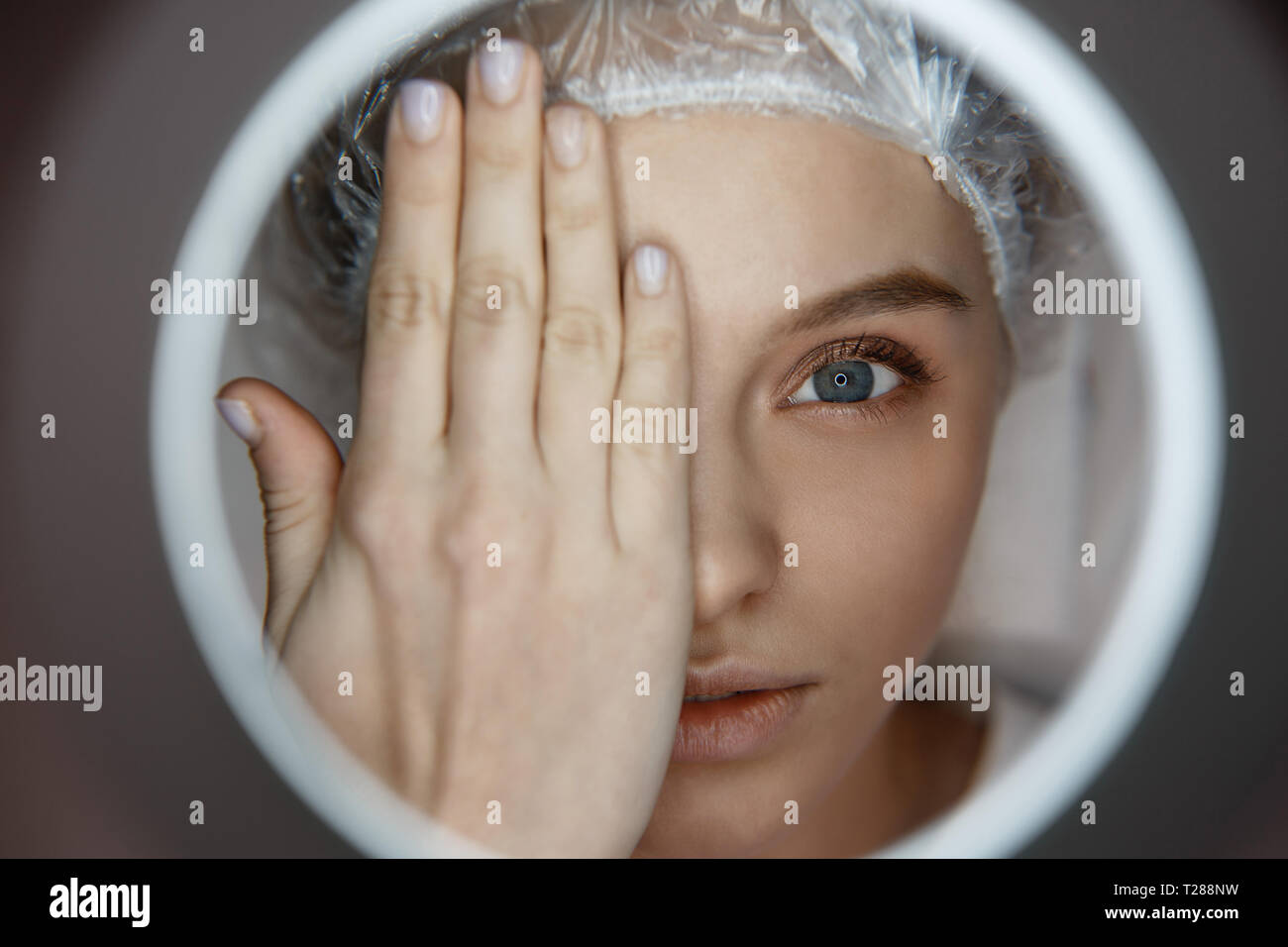 Close up young attractive woman lying and looking straight. She cover face prt with hand. Serious client look through light hole. - Stock Image