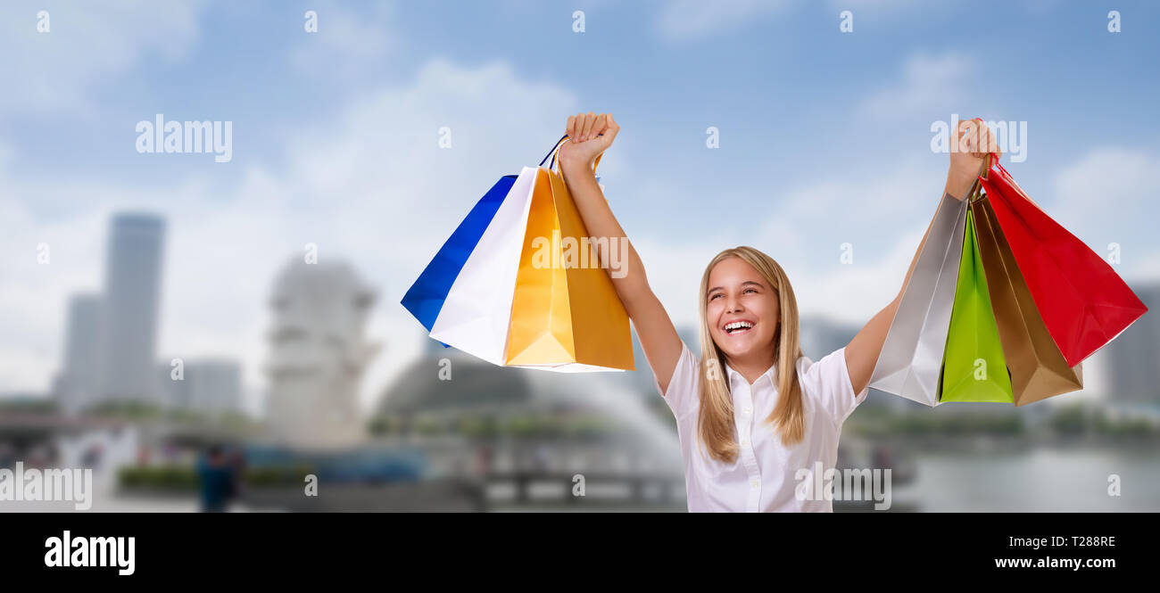 Shopping woman holding shopping bags above her head smiling during sale shopping. Cheerful young female shopper over Singapore city background - Stock Image