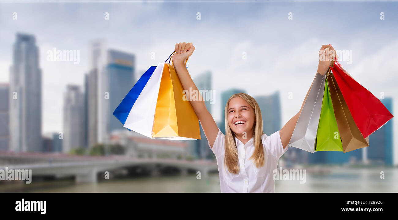 shopping,holiday,tourism and people concept - young cheerful girl with shopping bags with raised arms  over blurred city background - Stock Image