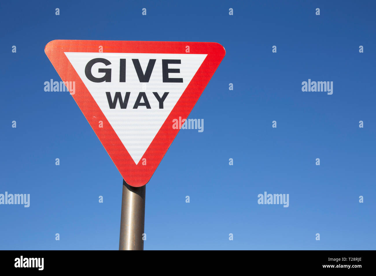 Give Way sign against blue sky Stock Photo