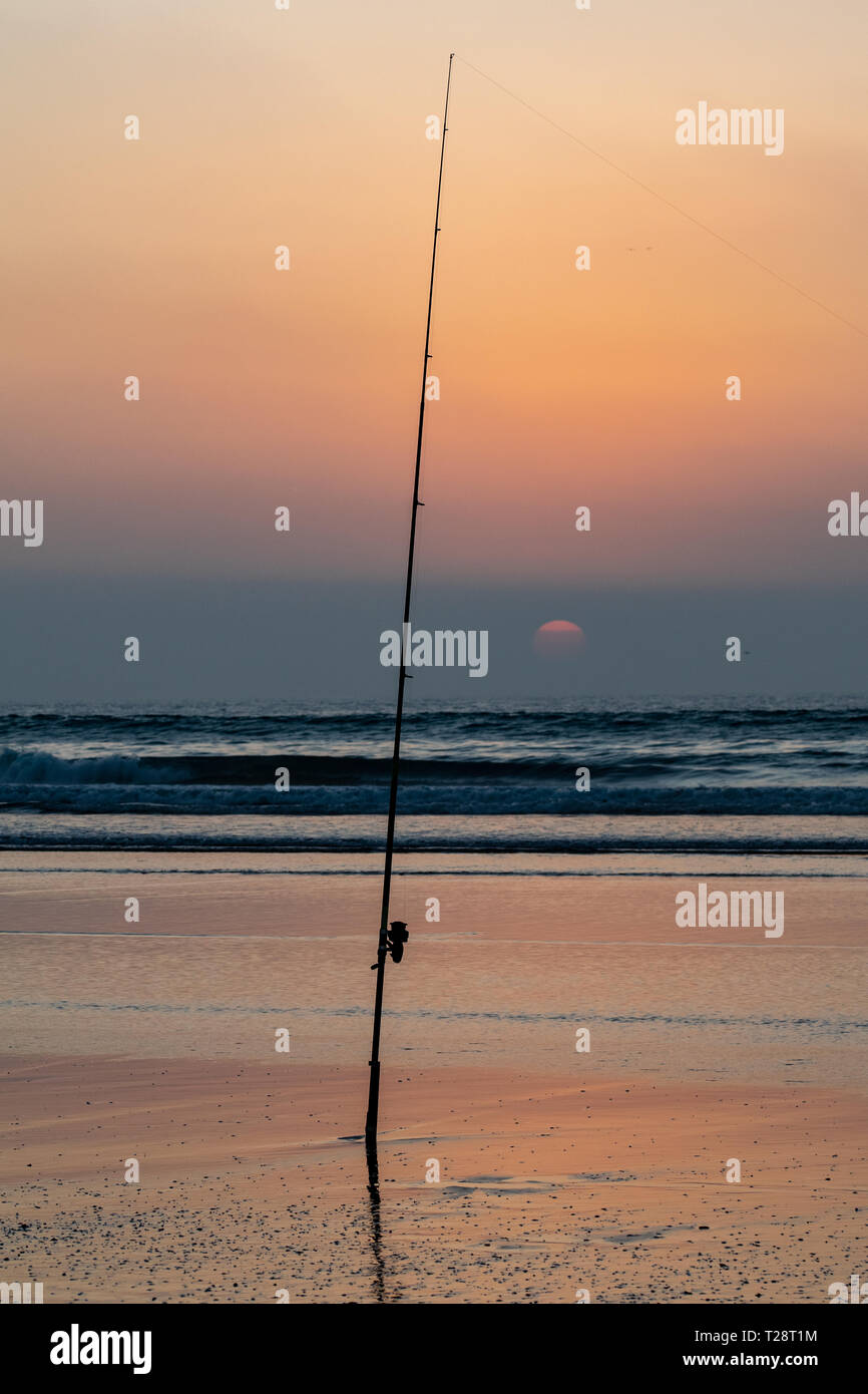 Silhouette of fishing rod at the edge of the Atlantic Ocean at sunset from Agadir beach, Morocco, Africa Stock Photo