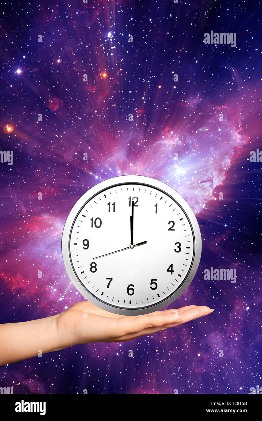 female hand holding a clock at twelve o'clock in her palm - Stock Image