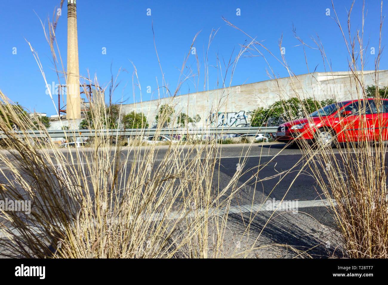 Road with red car, grass and chimney on the periphery, Spanish still life concept, Spain - Stock Image