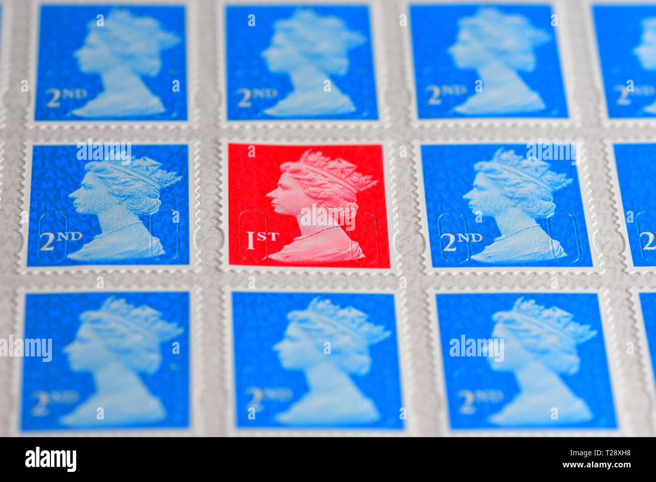 One red British 1st Class Stamp with blue 2nd class stamps - Stock Image