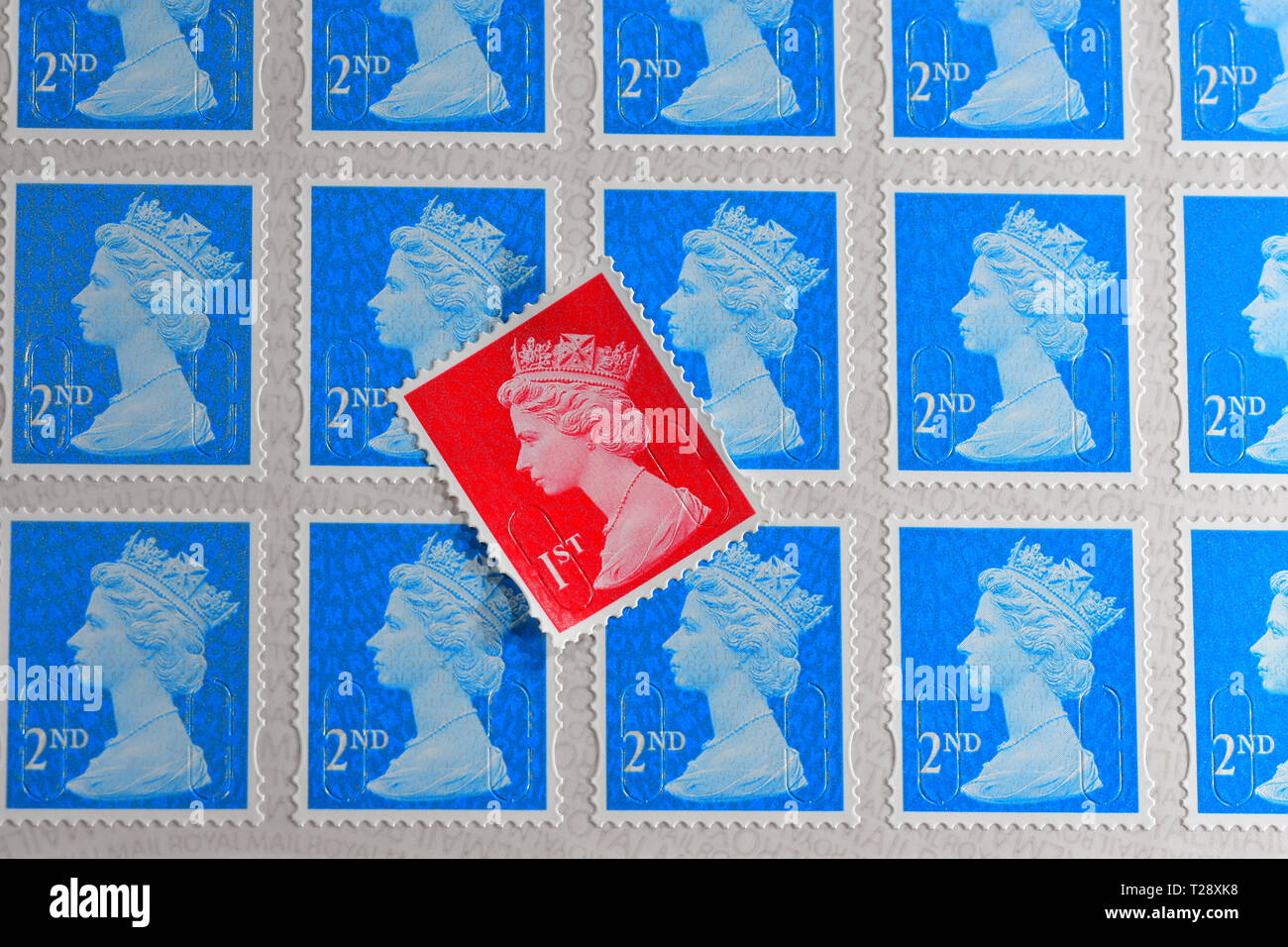 One red British 1st Class Stamp with blue 2nd class stamps Stock Photo