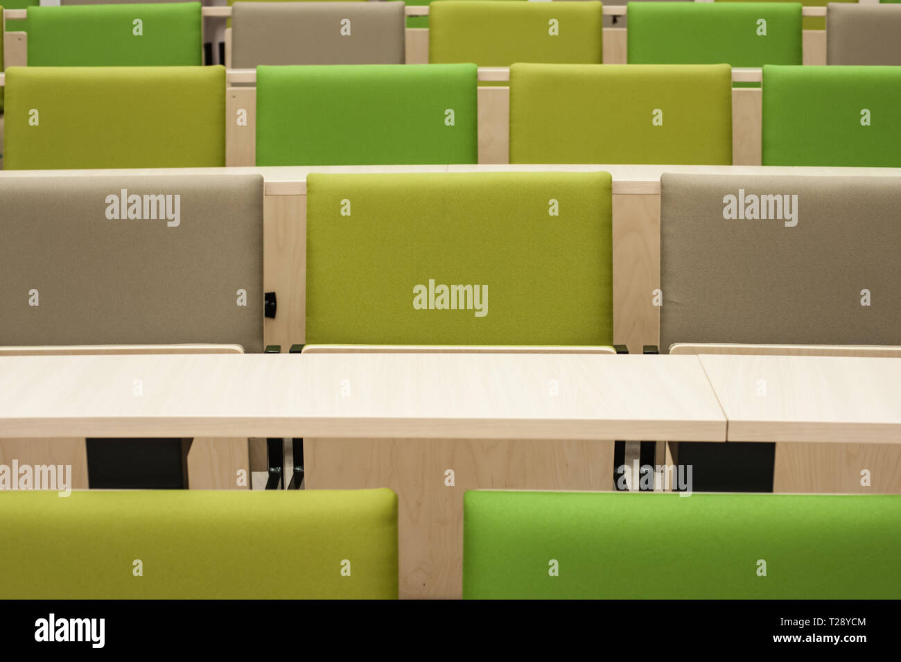 Colourful green seat covers in a university lecture theatre. - Stock Image