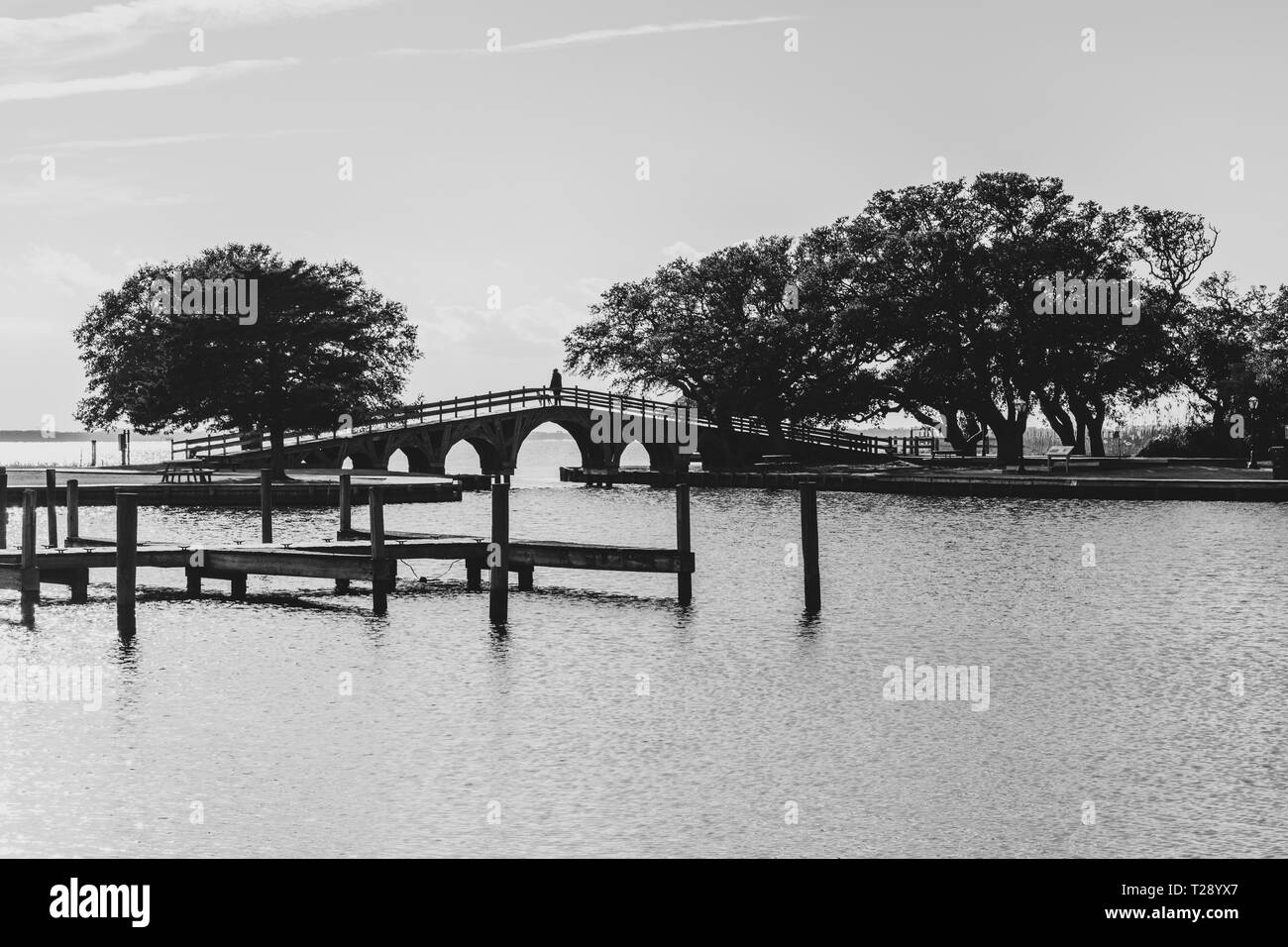 A woman and her dog are seen on a distant footbridge over water Stock Photo